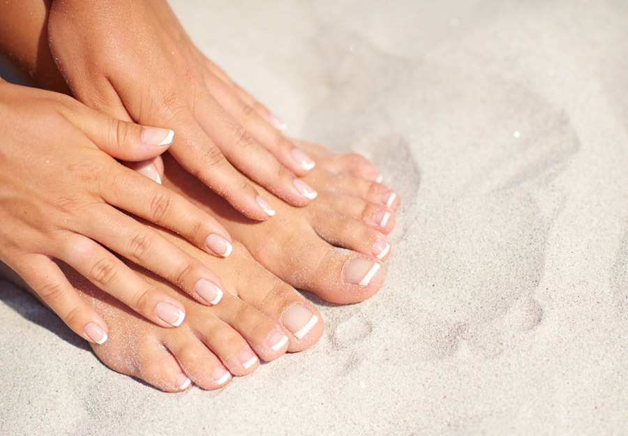 Manicure and pedicure over sand background on the beach