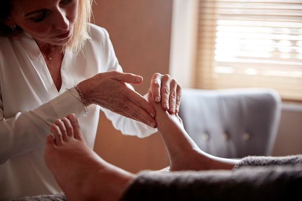 Reflexologist applying minute pressure to feet